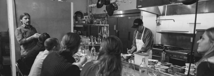 Chef preparing a meal in the Cultivating Spirits kitchen for a cooking class as participants watch.